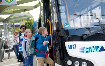Schulkinder steigen in Bus ein